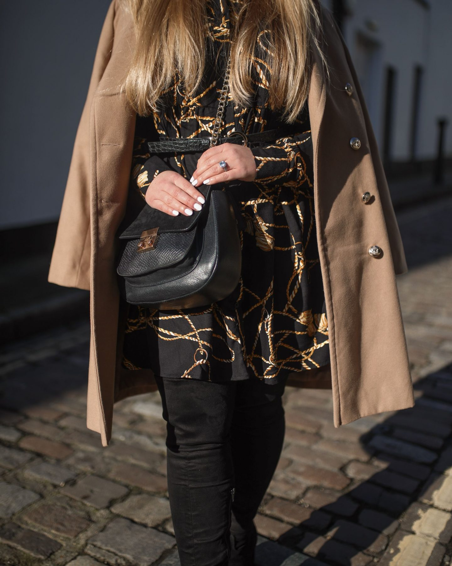 Katie Heath wearing black and gold dress, black boots and camel coat, KALANCHOE